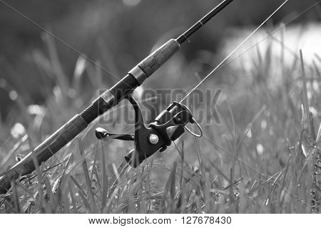 Fishing with rod on lake, black and white photo