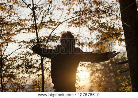 Young man in winter jacket standing with his arms spread widely in the autumn forest with low bright sunlight coming from behind him.