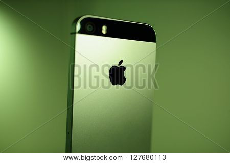 PARIS FRANCE - APR 21 2016: Rear view of the new Apple iPhone SE on green background with Apple logo and detail of the new Camera - it features updated processor 4K rear camera touch id retina display