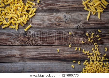 Mixed dried pasta selection on wooden background.