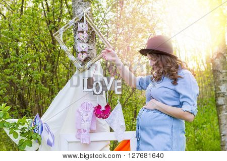 Beautiful pregnant woman outdoor with love text and children's clothing in her hand