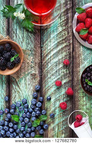 Herbal Tea And Berries On Green Rustic Table