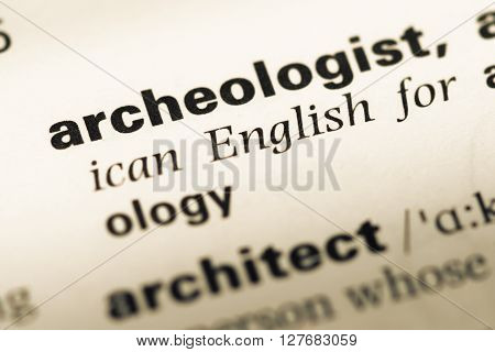 Close Up Of Old English Dictionary Page With Word Archeologist.