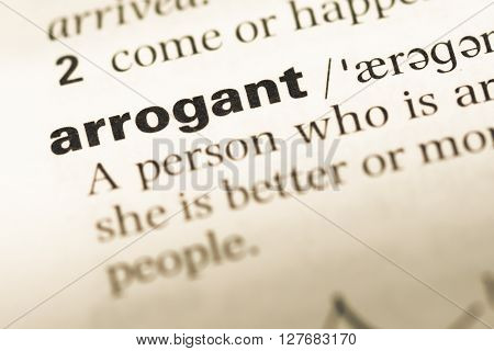 Close Up Of Old English Dictionary Page With Word Arrogant.