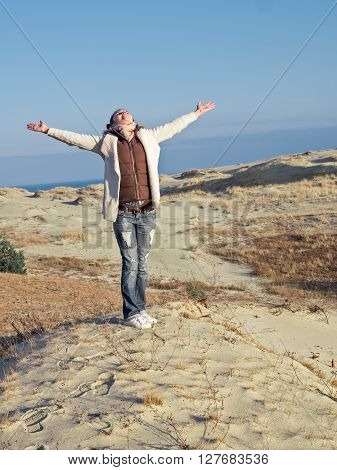 Happy girl on beach spring holiday in cheerful bliss enjoying the sunshine with arms outstretched