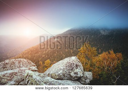 View of the foggy valley which glowing by sunlight. Dramatic scene and picturesque picture. Location place Carpathian, Ukraine, Europe. Beauty world. Retro and vintage style. Instagram toning effect.