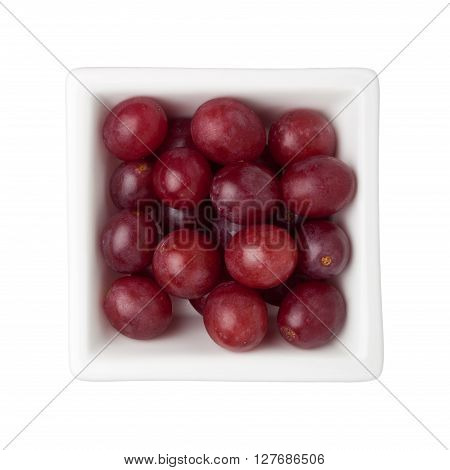 Red grapes in a square bowl isolated on white background