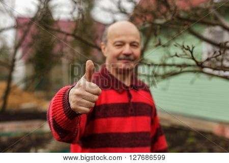 Elderly man with a mustache and a sweater showing thumb as an endorsement