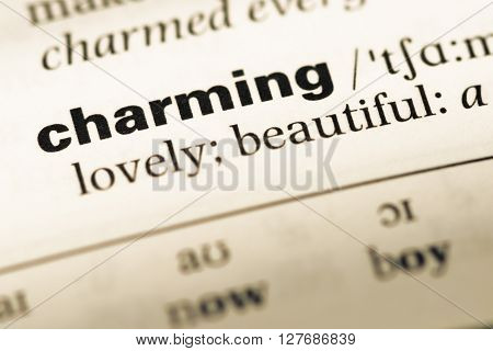 Close Up Of Old English Dictionary Page With Word Charming.