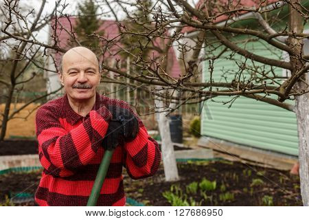 Elderly Man With A Garden Tool Is Resting After Work.