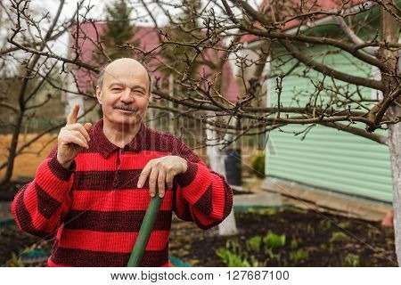 Elderly Man With A Garden Tool Gives Tips And Tricks For Working