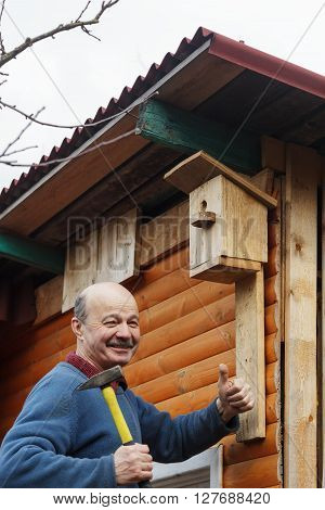 senior with a mustache attaches birdhouse to the barn