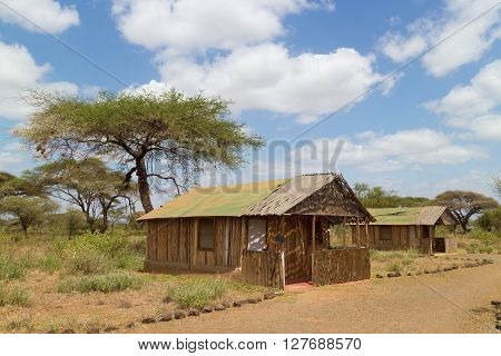 Safari vacation. Woman enjoying natural enviroment from traditional african tourist lodge.