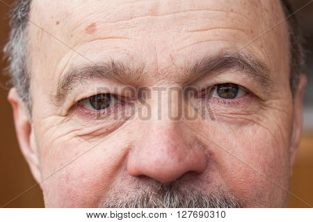 Pensioner looking intently ahead. Tired eyes from life