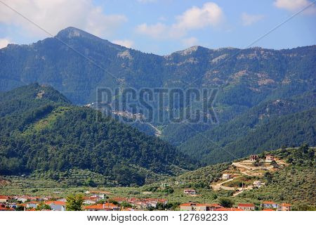 beautiful mountain range, mountains of different heights, covered with forests, greenery, village, blue sky with clouds