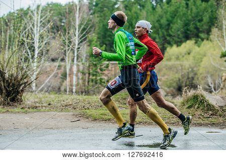Chelyabinsk Russia - April 23 2016: couple of young male athletes running down road during Half marathon in woods