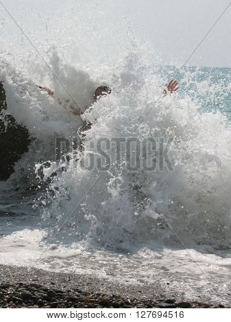 photo splashes of the waves. a man stands holding up hands in sea foam