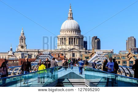 London England - April 20 2016 - St Paul's Cathedral and Millennium Bridge with tourists and locals walking with motion blur on a sunny and cloudless afternoon