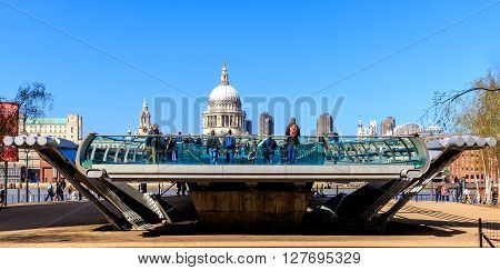 London England - April 20 2016 - St Paul's Cathedral and one head of the Millennium Bridge with tourists and locals walking and taking pictures on a sunny and cloudless afternoon
