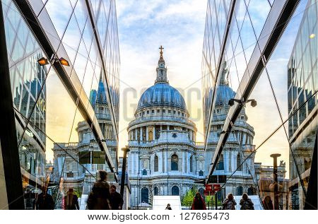 London England - April 20 2016 - View of St Paul's Cathedral from the One New Change building. Blue orange sky and Cathedral are reflected in the glass of the buildings.