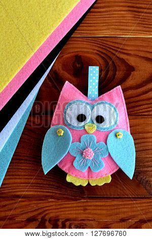 Colorful felt owl toy. Handmade children's crafts. Felt sheets, sewn toy owl on a wooden table. Close-up. DIY concept
