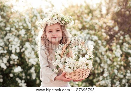 Cute baby girl 3-4 year old wearing floral wreath outdoors. Holding basket of flowers. Looking at camera. Childhood.