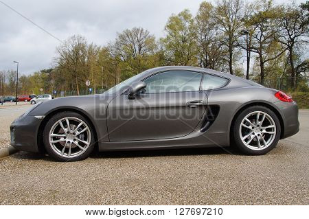 Soest, The Netherlands - April 29, 2016: Gray R Porsche 981 cayman coupe parked on a public parking lot in the city of Soest.