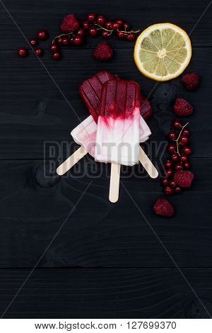 Berry coconut ice pops - popsicles - over old black rustic wooden background. Top view copy space