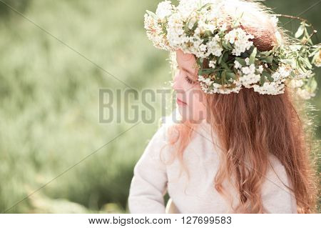 Cute baby girl 3-4 year old wearing flower wreath outdoors closeup. Looking away. Summer time.