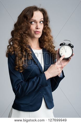 Puzzled Business Woman Holding An Alarm Clock