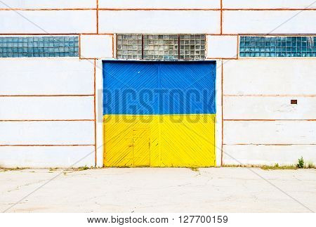 Wall of ancient warehouse with door painted in ukrainian flag colors - blue and yellow. Ukrainian flag on the background of old locked doors