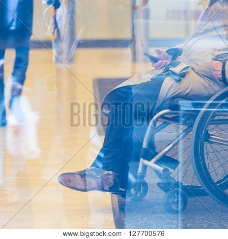 Handicapped male businessman on a wheelchair using smartphone. Disabled people active for life.