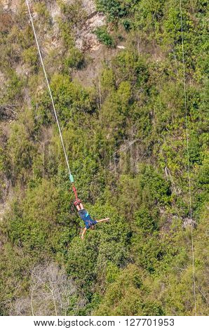 BLOUKRANS BRIDGE SOUTH AFRICA - MARCH 2 2016: An unidentified male bungee jumper in the worlds highest commercial bungee jump at the Bloukrans Bridge at 216 meter the highest bridge in Africa