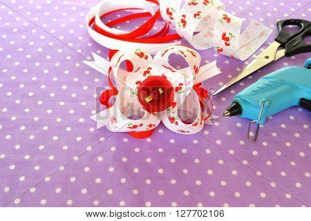 Bright bow of ribbon, children hair accessory, ribbon set, scissors, hot glue gun