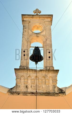 A white bell tower of color with a bell an eye of ox