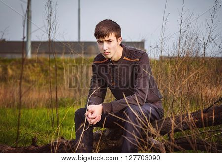 Sad and frowning young man sitting alone on a tree trunk with dry brush around him