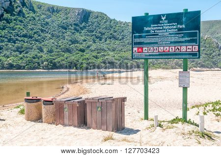 NATURES VALLEY SOUTH AFRICA - MARCH 2 2016: Information board and refuse bins next to the lagoon at the mouth of the Groot River at the town of Natures Valley