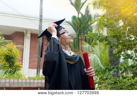 Cheerful asian university graduate in the college