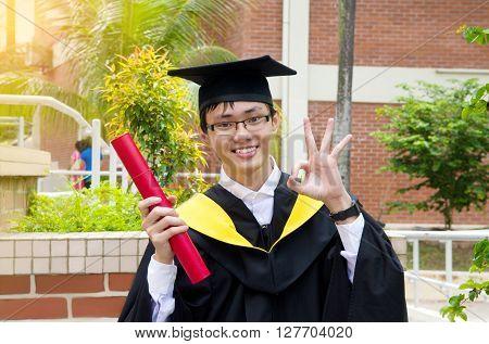 Cheerful asian university graduate looking at camera
