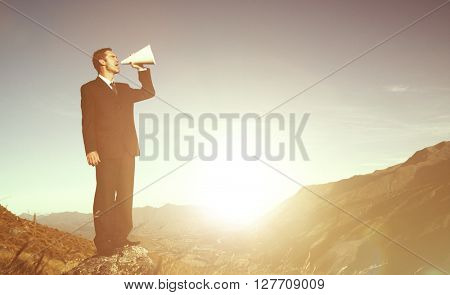 Businessman shouting on the top of the mountain.