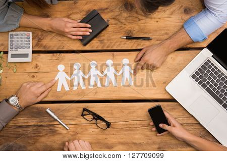 Paper man chain holding hands. Teamwork concept with paper chain, group of people holding hands held over wooden table. Businesspeople holding paper man chain depicting unity and team work.
