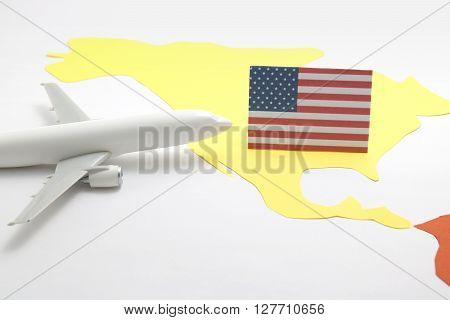Trip by airplane to United States of America. Miniature airplane flies toward the flag of United States of America.