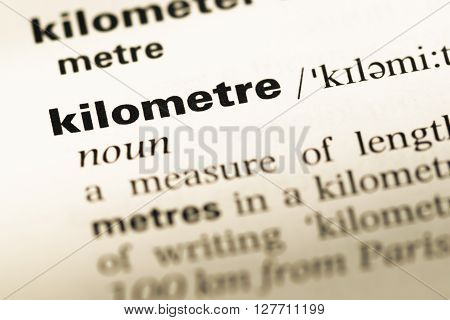 Close Up Of Old English Dictionary Page With Word Kilometre.