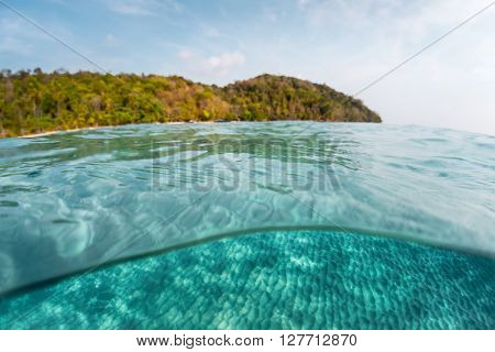 Tropical calm sea with island on the horizon and underwater view of the sandy bottom with wavy pattern. Focus underwater