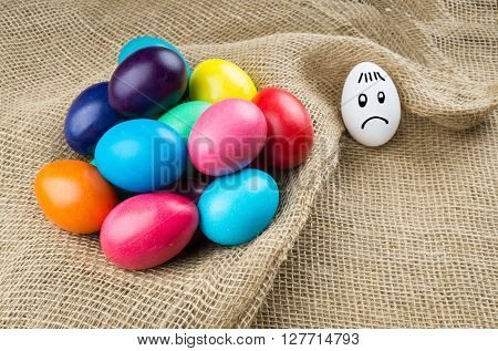 Sad different white egg and group of colorful easter eggs on sackcloth background