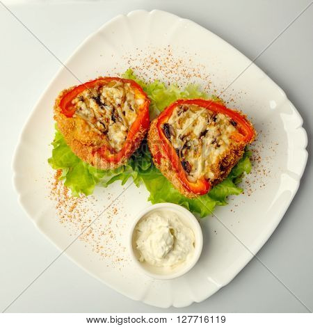 multicolor stuffed bell pepper filled with ground meat, rice, onion and parsley on white plate ** Note: Soft Focus at 100%, best at smaller sizes