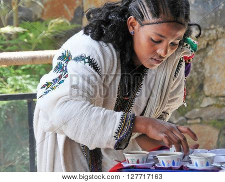Axum Ethiopia - September 28 2012: Young Ethiopian woman in traditional clothing is serving coffee during a traditional coffee ceremony. This ritualised ceremony is an important part of the Ethiopian culture.