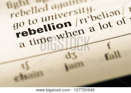 Close Up Of Old English Dictionary Page With Word Rebellion.