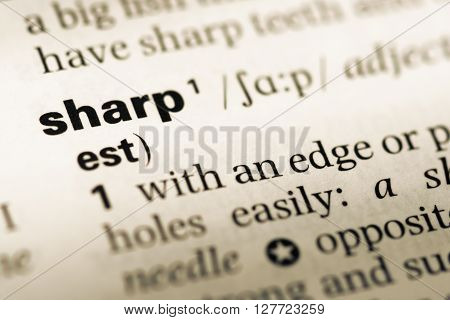 Close Up Of Old English Dictionary Page With Word Sharp.