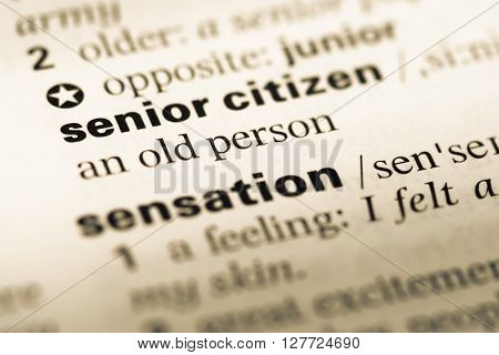 Close Up Of Old English Dictionary Page With Word Senior Citizen.